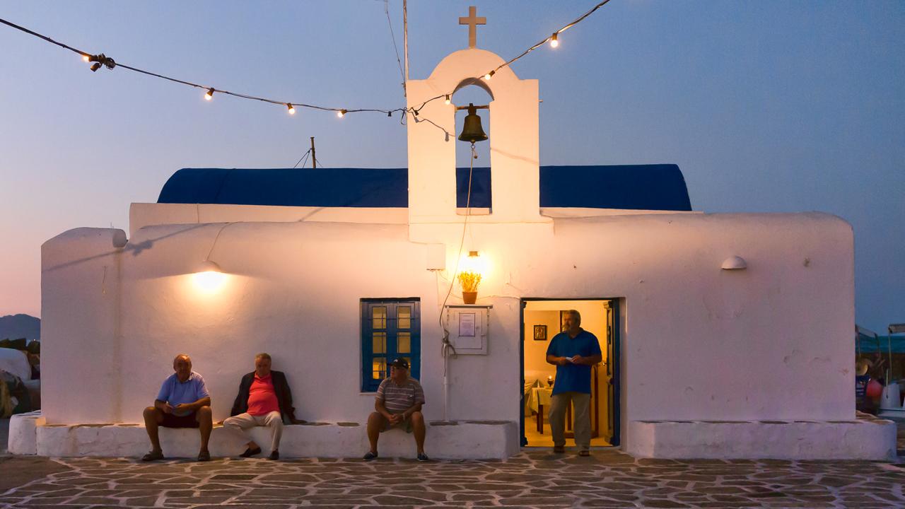Paros, Cyclades, Grèce : pécheurs devant l'église de Saitn Nicolas dans le port de Naoussa harbour